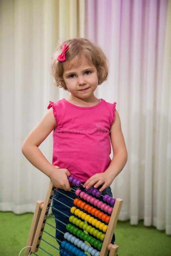 Flicka som spelar med färgställningar royaltyfri foto