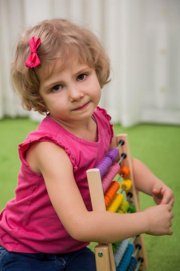 Flicka som spelar med färgställningar arkivbild