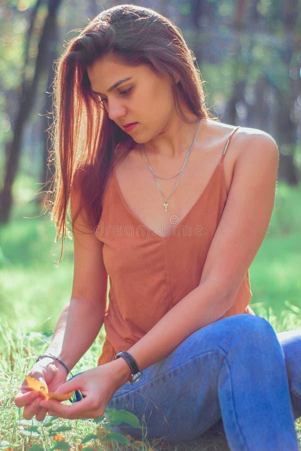 flicka som spelar med höstsidor mot bakgrunden av skogen arkivbild