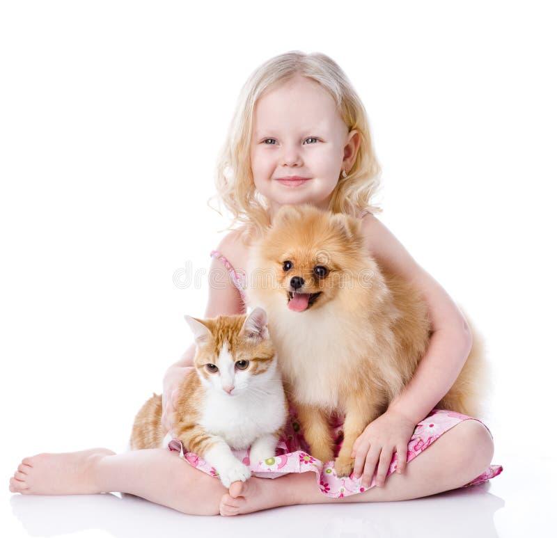 Flicka som spelar med husdjur - hund och katt. royaltyfri fotografi