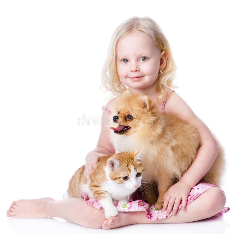 Flicka som spelar med husdjur - hund och katt arkivbild