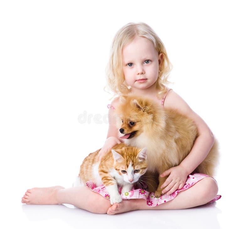 Flicka som spelar med husdjur - hund och katt se kameran isolate royaltyfri fotografi