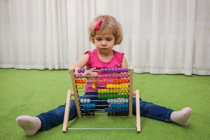 Flicka som spelar med kulöra räkningar arkivfoto