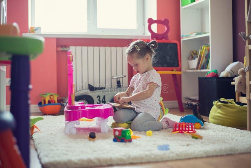 flicka som spelar med leksaker i barnrummet arkivbild