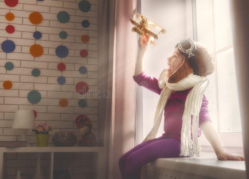 Flicka som spelar med leksakflygplanet fotografering för bildbyråer
