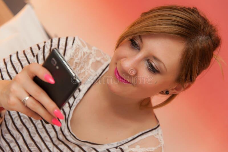 Flicka som spelar med mobiltelefonen royaltyfria bilder