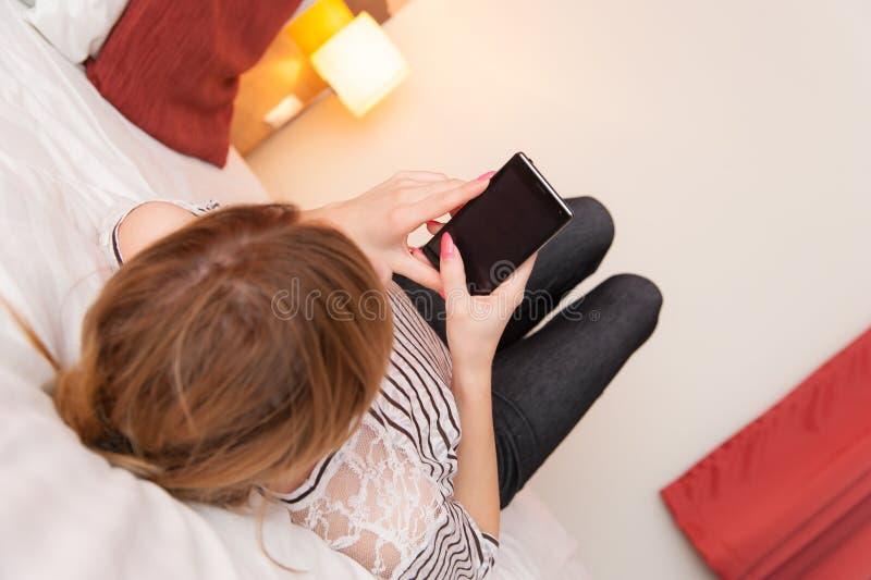Flicka som spelar med mobiltelefonen arkivfoto