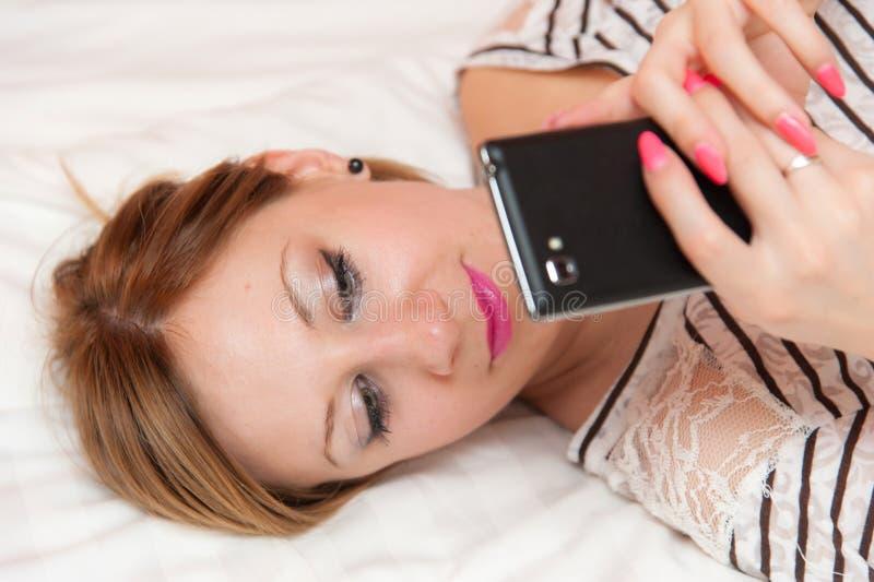 Flicka som spelar med mobiltelefonen royaltyfri fotografi