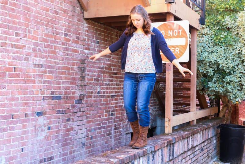 Flicka som spelar och balanserar på väggen för röd tegelsten royaltyfria foton