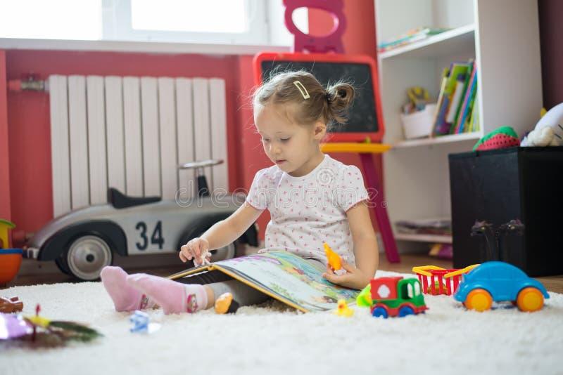 Flicka som spelar och läser i barnrummet royaltyfria foton