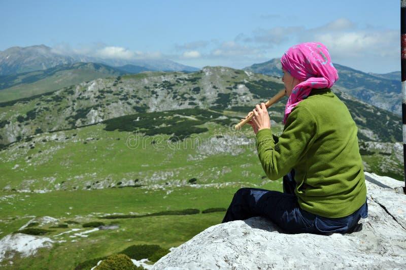 Flicka som spelar på flöjten i bergen arkivfoton