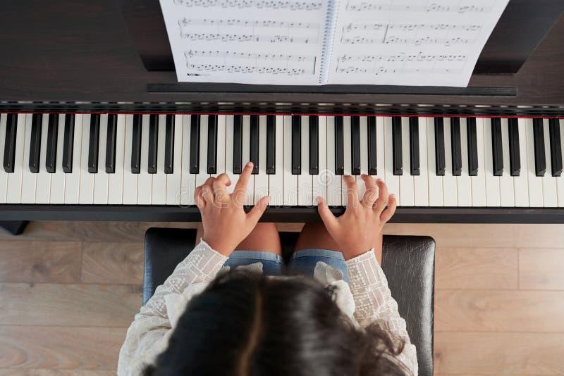 Flicka som spelar på musikinstrumentet arkivfoto