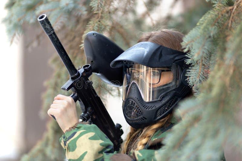 Flicka som spelar paintball i overaller med ett vapen arkivbilder