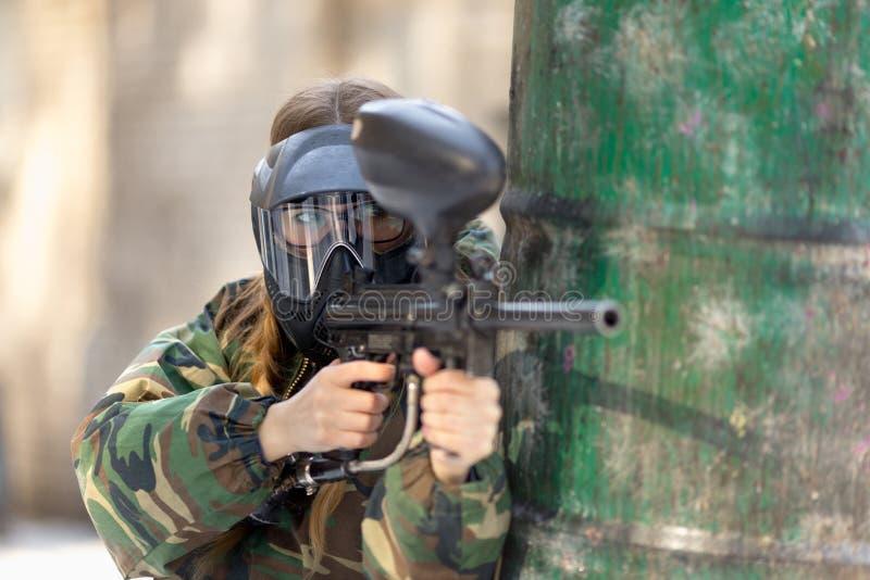 Flicka som spelar paintball i overaller med ett vapen arkivfoton