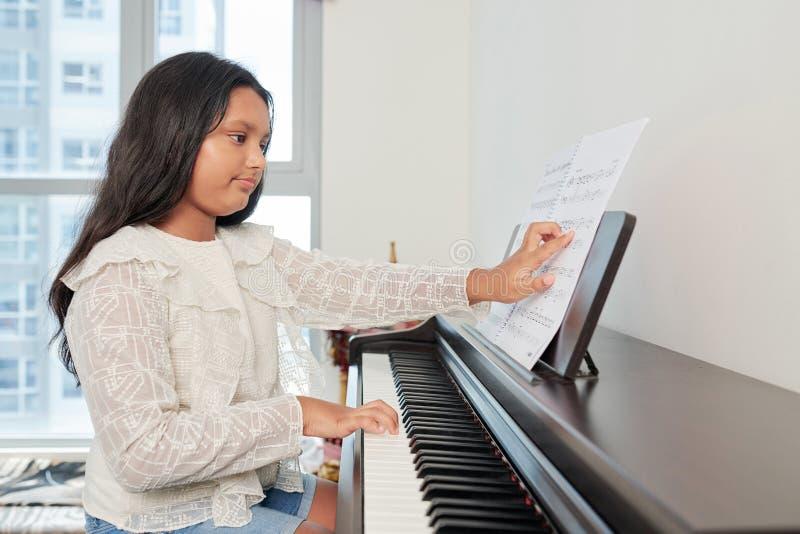 Flicka som spelar sammansättningen på piano arkivfoton