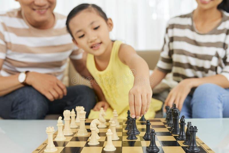 Flicka som spelar schack med föräldrar royaltyfria bilder
