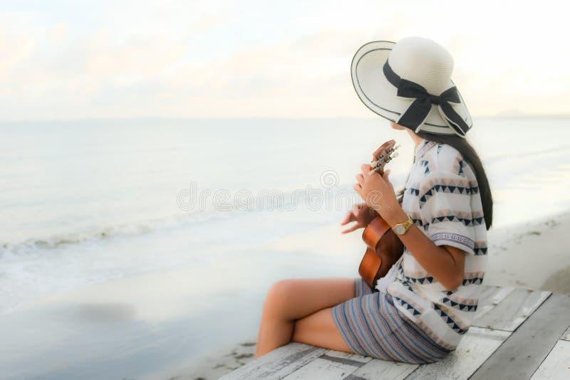 Flicka som spelar ukulelet i stranden royaltyfria bilder