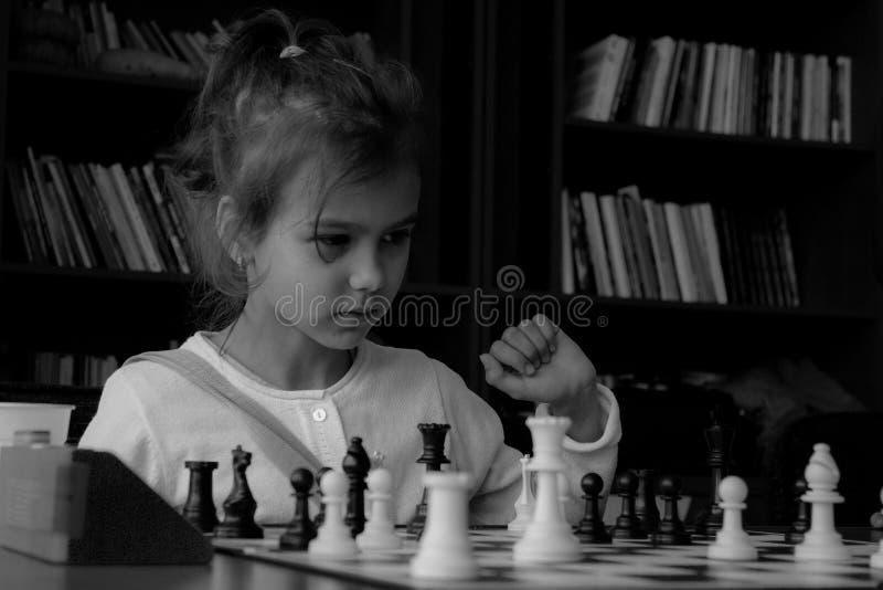 Flicka som spelar verkligt schack royaltyfria foton