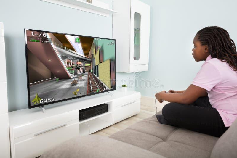Flicka som spelar videospelet med styrspakar royaltyfri fotografi