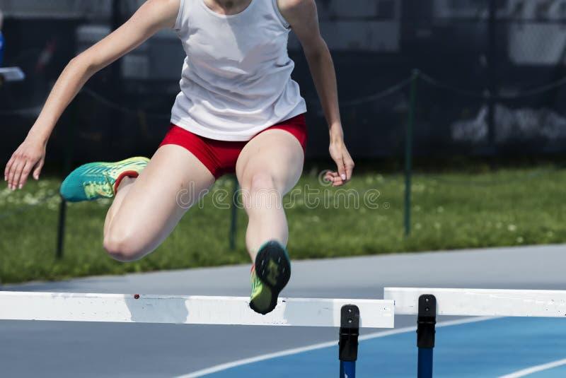 Flicka som springer de 400 häckarna arkivbilder