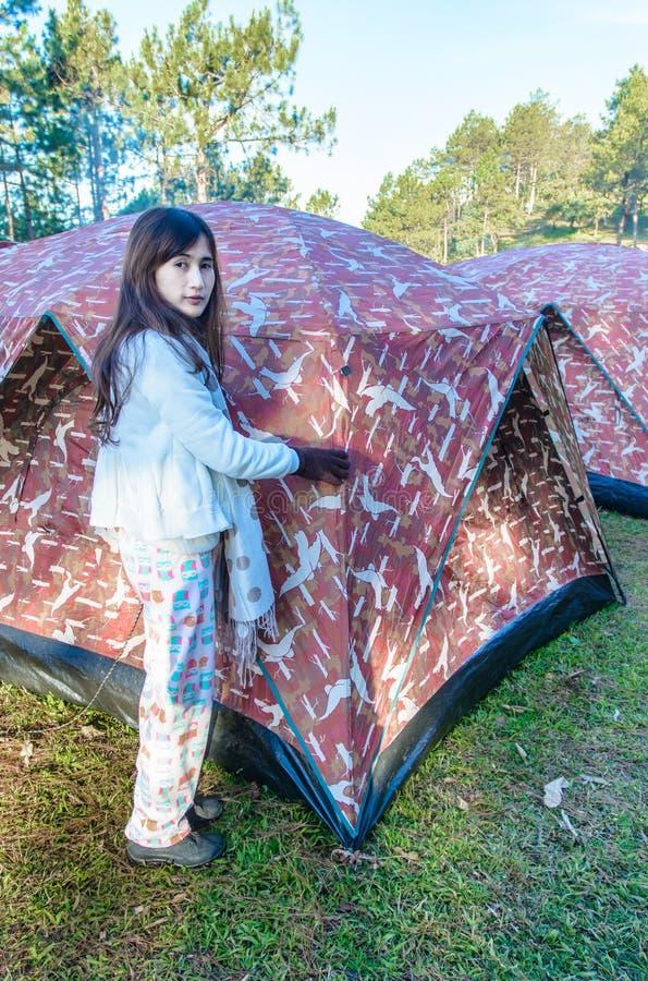 Flicka som ställer in ett tält royaltyfria bilder