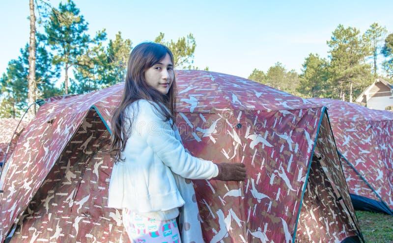 Flicka som ställer in ett tält royaltyfri foto