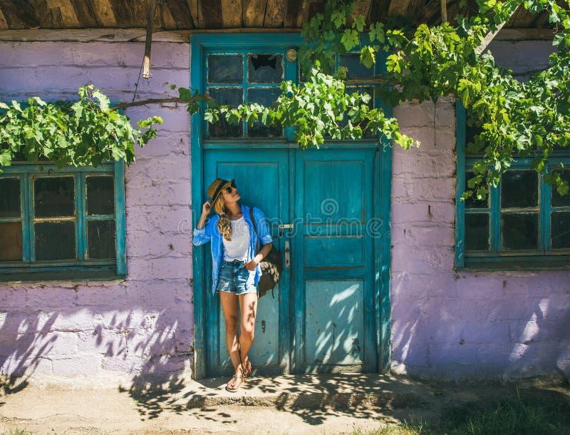 Flicka som står den near purpurfärgade väggen i turkisk by i sommar royaltyfri foto