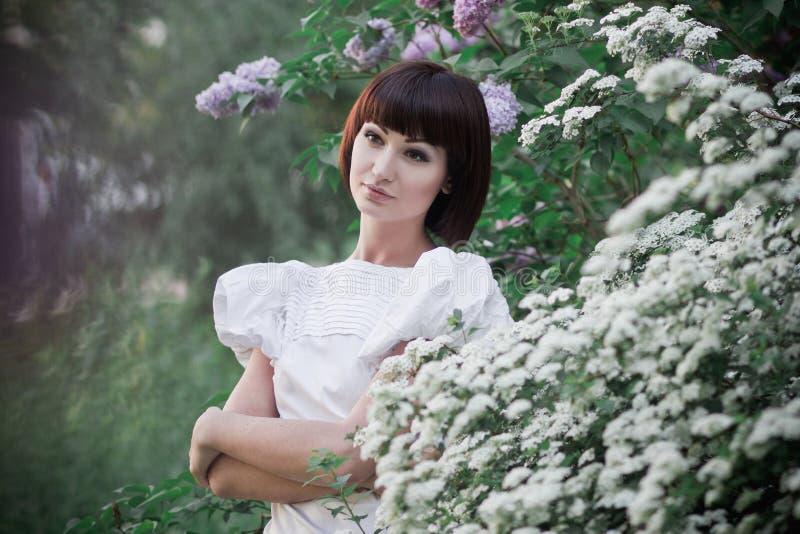 Flicka som står near lilor royaltyfria foton
