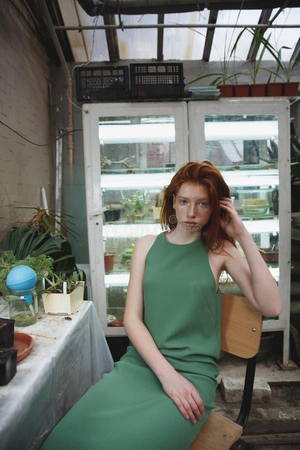 Flicka som stirrar på kameran i grönska arkivbild