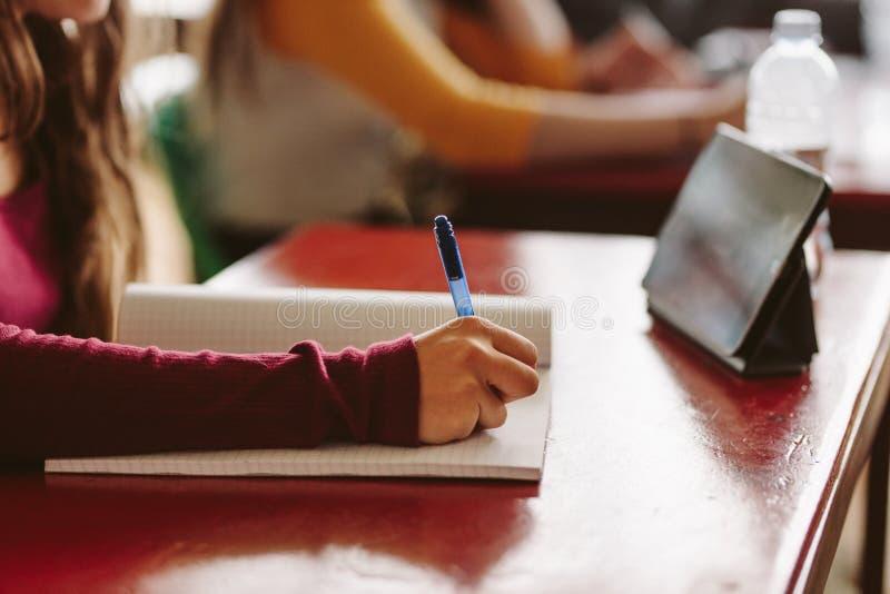 Flicka som studerar i universitetklassrum arkivbild