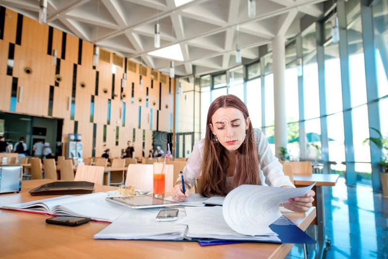 Flicka som studerar på universitetkantin fotografering för bildbyråer