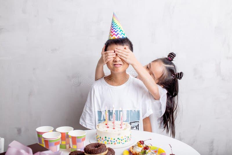 Flicka som täcker hans väns ögon med händer för att göra en överraskning arkivfoto