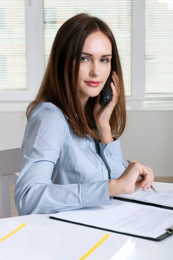 Flicka som talar på en telefon, medan arbeta med dokument arkivbild