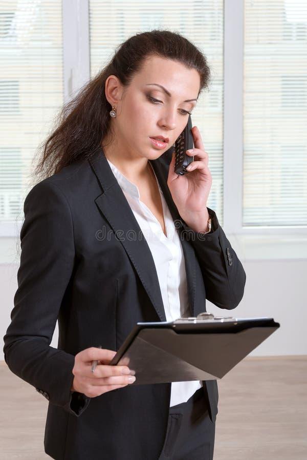 Flicka som talar på telefonen, medan läsa information royaltyfria foton
