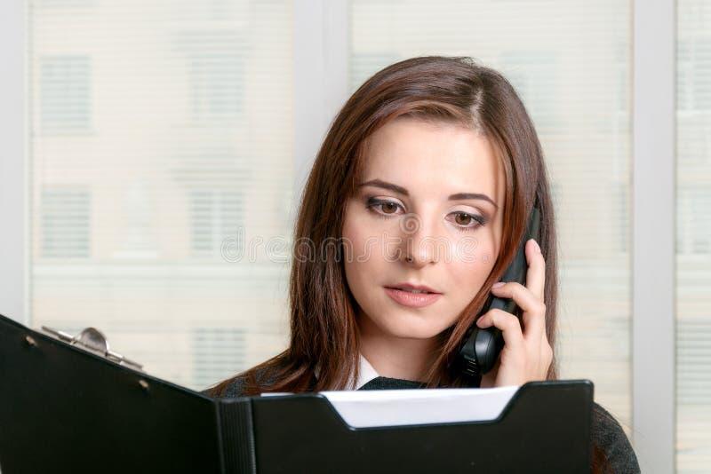 Flicka som talar på telefonen, medan läsa texten av den öppna folen royaltyfri bild