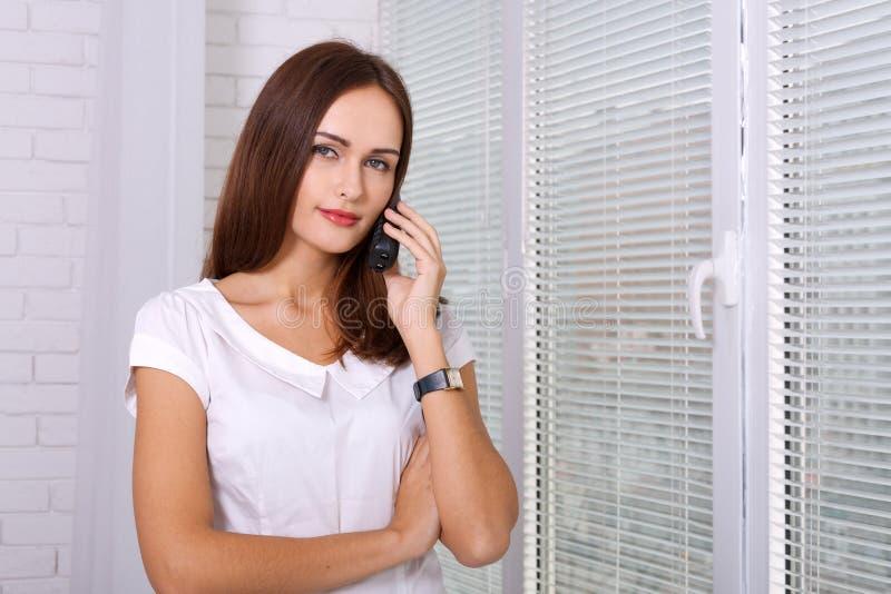 Flicka som talar på telefonen, medan stå nära fönstret arkivbild
