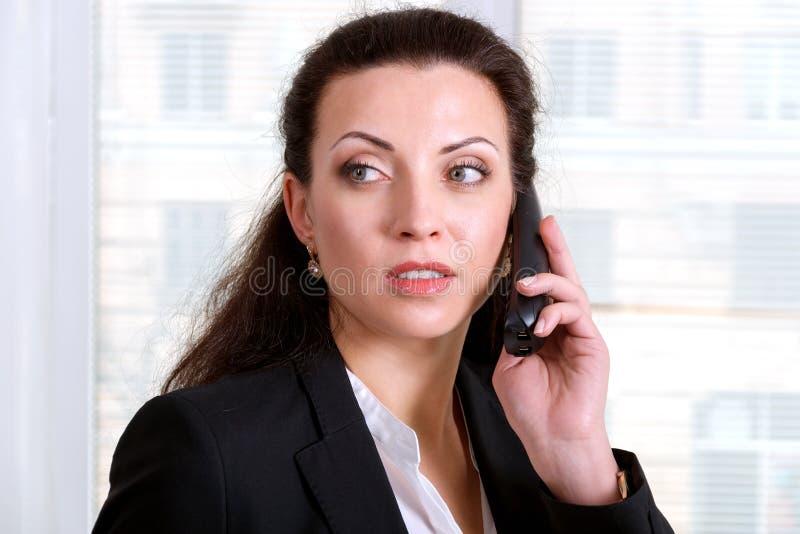 Flicka som talar på telefonen och bort ser royaltyfri foto