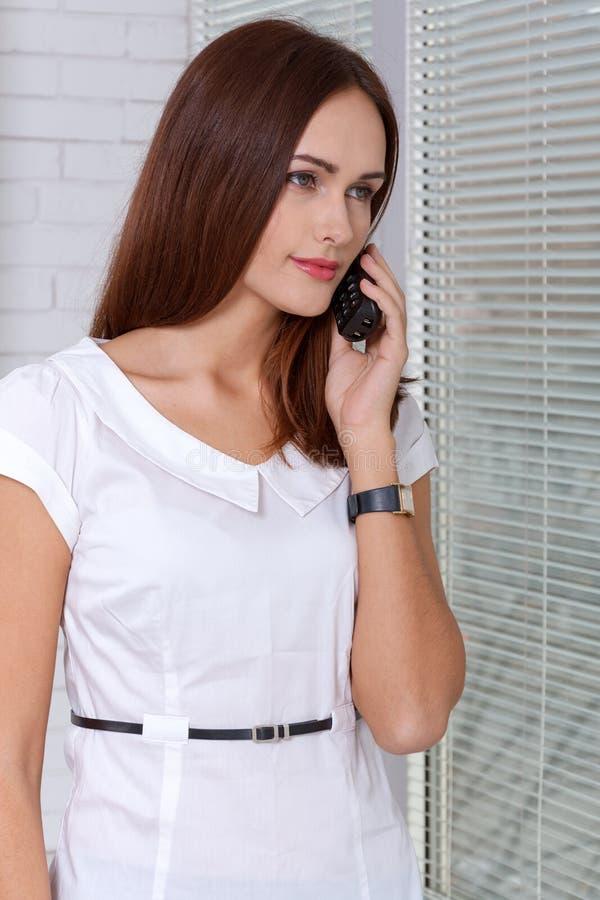 Flicka som talar på telefonen som ut ser fönstret arkivfoton