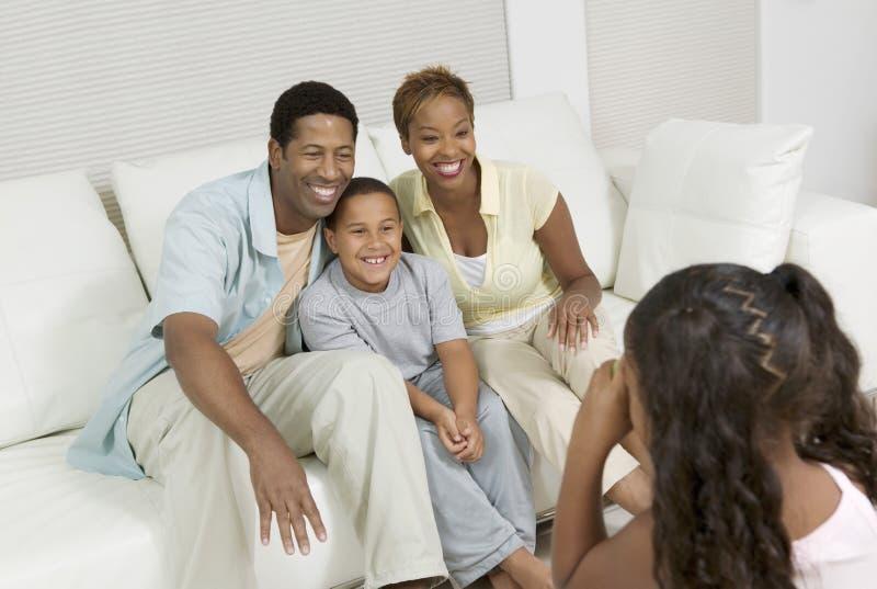 Flicka som tar bilden av familjen på soffan i vardagsrum royaltyfri bild