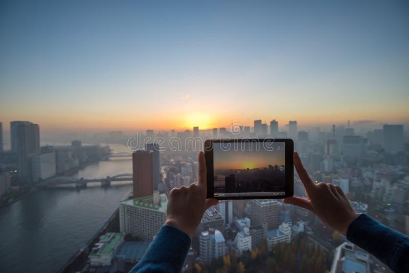Flicka som tar bilden av Tokyo med minnestavlan royaltyfri bild