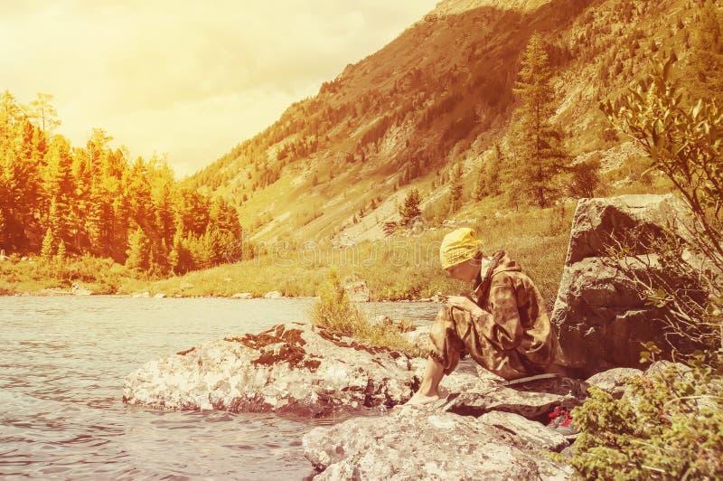 Flicka som tar bilden vid mobiltelefonen på sjön på solnedgång royaltyfria foton