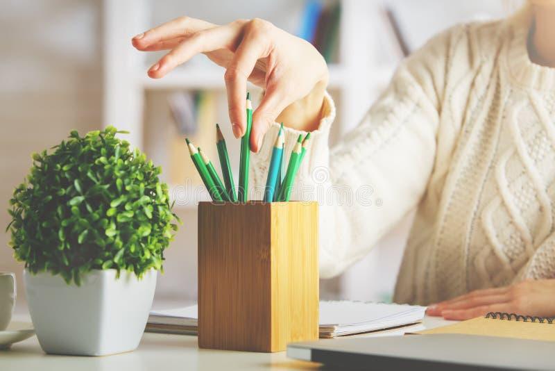 Flicka som tar den gröna blyertspennan arkivbilder