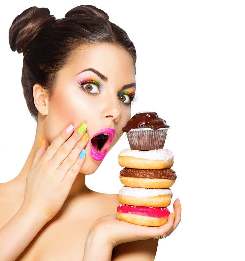 Flicka som tar färgrika sötsaker och färgrika donuts royaltyfri foto