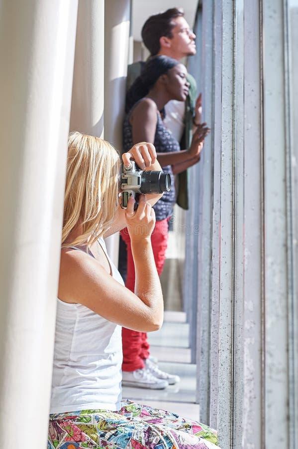 Flicka som tar fotoet ut ur fönster med folk i bakgrund royaltyfri bild