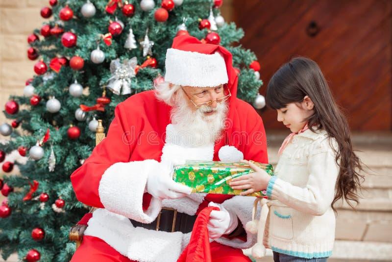Flicka som tar gåvan från Santa Claus arkivfoton