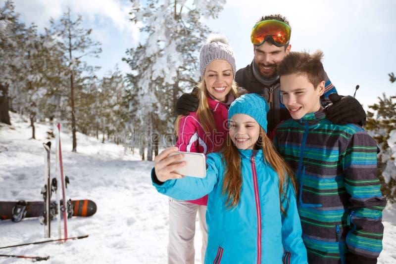 Flicka som tar selfie med familjen på skidåkning royaltyfria foton
