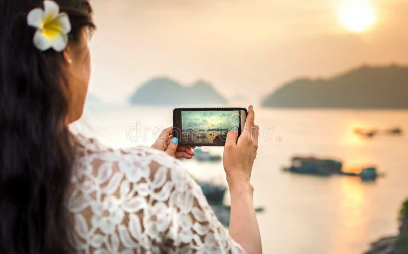 Flicka som tar sjösidasolnedgångbilden med smartphonen arkivbilder