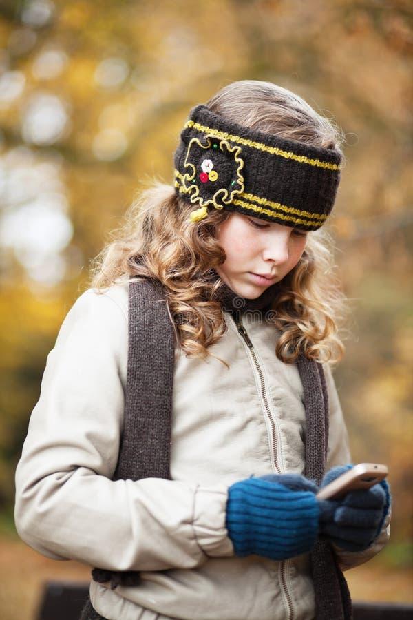 Flicka som texting med mobiltelefon i en höstpark arkivbild