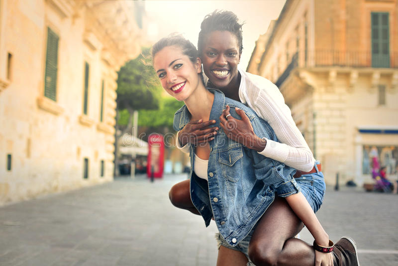 Flicka som tillbaka bär en vän på henne royaltyfri bild
