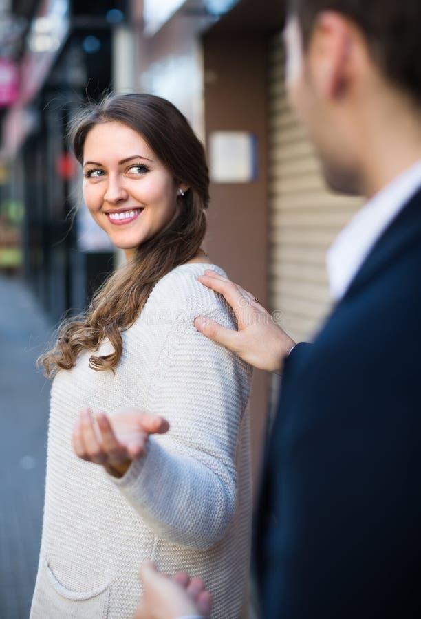 Flicka som tillbaka ler på mannen royaltyfri foto